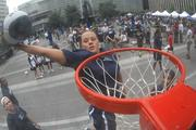 A Xavier women's basketball player dunks on the hoop set up on Fountain Square Monday afternoon.