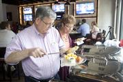 Fred, left, and Marian Orringer help themselves at the buffet at Keystone Bar & Grill Clifton. The restaurant hosted a media and friends and family night on Saturday. Fred Orringer installed the restaurant's equipment.