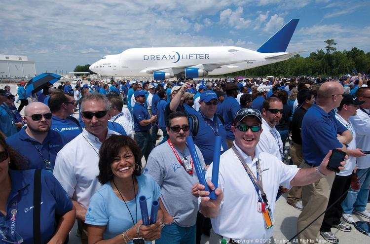 """TRIUMPHANT: Boeing employees in South Carolina celebrate as the first Charleston-built 787 Dreamliner rolls out of the assembly plant in April 2012. In the background, a symbol of Boeing's geographic reach: a """"Dreamlifter,"""" which is used to shuttle 787 sections between the South and the Puget Sound region."""