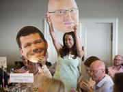 Members of No. 1 company Blueprint Consulting Services hold up big head cut-outs of their executives Ryan Neal, left, and Kyle Wagner as the hear the news that the company has made the top of The List.