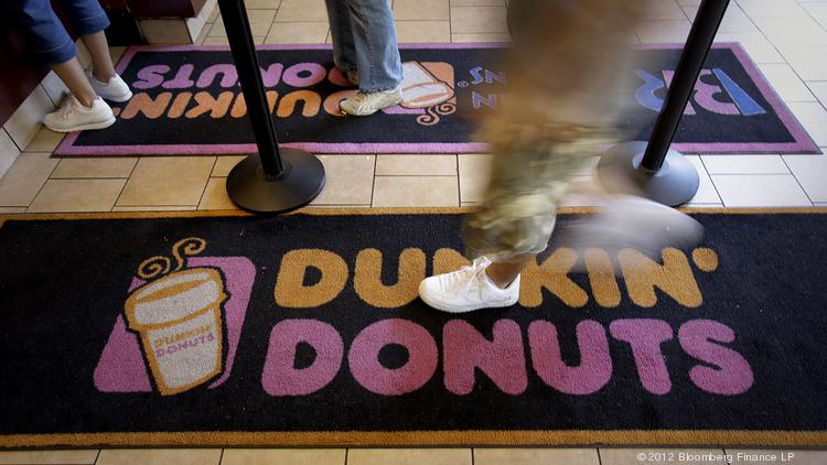 A customer enters at a Dunkin' Donuts store in New York, U.S., on Wednesday, July 25, 2012. Dunkin' Brands Group Inc. is scheduled to release earnings data on July 26. Photographer: Scott Eells/Bloomberg