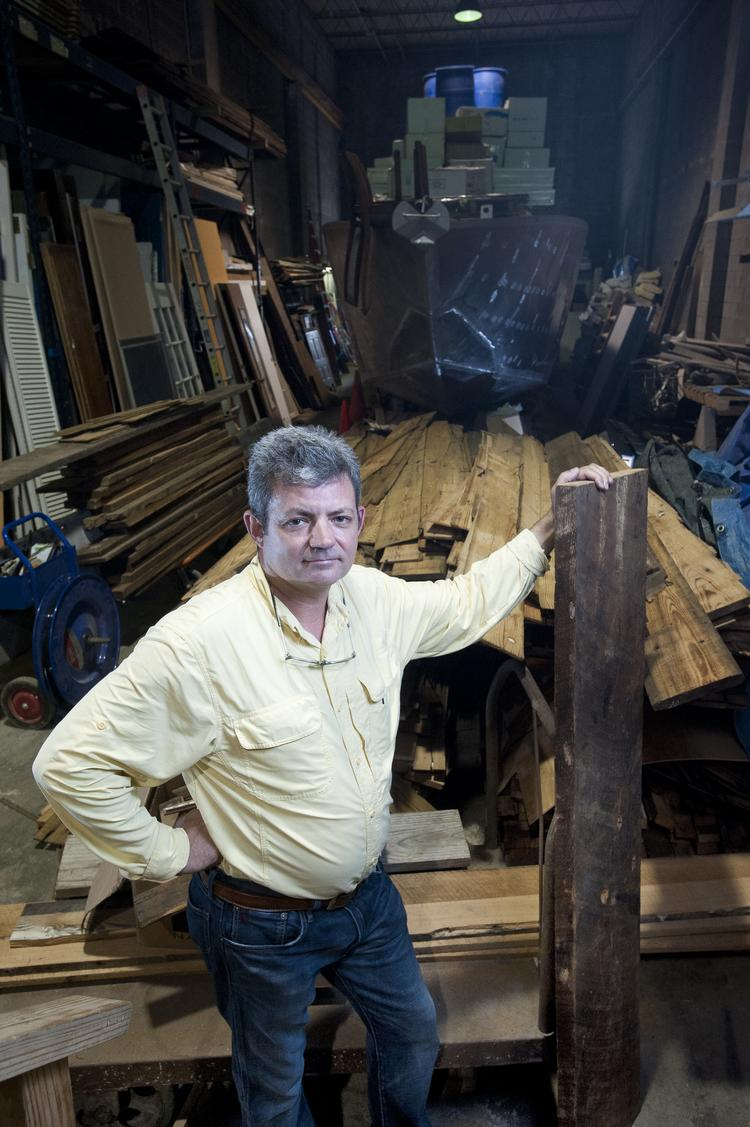 Kiel Thomson, president of Kiel Thomson Co., stood in a storage area that houses two large boats still under construction and salvaged wood from around the country that he repurposes in his construction business.