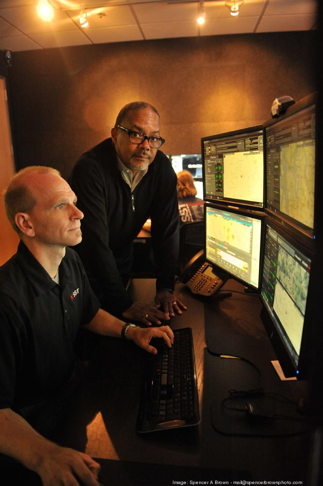 Ralph Clark (standing) works with manager Scott Beisner to steer SST from being tech-focused to analyzing data customized to police crime-fighting needs.