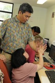 Mark Conching, immediate past president of the Ohana Komputer board, gives Kay Kidani a high five for her successes on mastering a level on a computer program at the Makiki Community Library. Ohana Komputer partnered with Lanakila Pacific Day Program to provide computer training services to adults who are developmentally challenged.