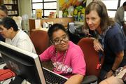 Gigi Davidson, right, executive director with Ohana Komputer, helps Madeline Gungab at the Makiki Community Library last month. Ohana Komputer partnered with Lanakila Pacific Day Program to provide computer training services to adults who are developmentally challenged.