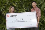 """HUGS, the local nonprofit helping Hawaii families with seriously ill children, received $22,000 from Zippy's """"Have A Heart for HUGS"""" promotion. Proceeds from Kokua Pacs, HUGS hearts and wristbands sold, along with contributions customers made in collection boxes, were donated to HUGS last month. From left; Julie Ho of HUGS accepts a check from Paul S. Yokota, FCH Enterprises president."""