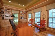 The study has a tray ceiling, hardwood floor and built-in shelves.