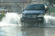 An SUV drives through flooding in Miami Beach after extreme high tides.