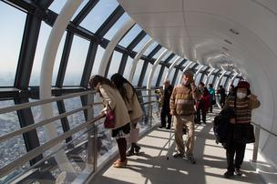 Visitors walk through the viewing deck of the Tokyo Skytree, operated by Tobu Railway Co., in Tokyo, Japan. Japan returned to growth in the fourth quarter, bolstering Prime Minister Shinzo Abe's campaign to end 15 years of deflation and revive the world's third-biggest economy.