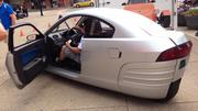Another interested local checks out the Elio interior at a demonstration on the South Side. The car seats two in tandem.