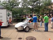 Elio motors test driver Kevin Modzelewski helps a Pittsburgher into the cockpit of the new Elio three-wheeled vehicle.