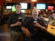 Patrick Kirk (left), director of beverage innovation at Buffalo Wild Wings, and Matt Licklider, Master Brewer at Redhook Brewery, in Buffalo Wild Wings on the University of Minnesota campus.