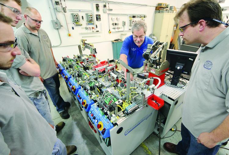 Electronic technology instructor MIke Breskovich, center, shows students the features of a programmable logic controller.
