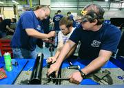 From left, diesel technology students Rick Kaposy, 46; Ian Shearer, 21; and Shane Powers, 40, rebuild a hydraulic cylinder at Rosedale Technical Institute.
