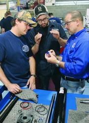 Diesel technology instructor Mark Simoneau, right, advises students Shane Powers, 40, left, and Kyle Hebedank, 20, on how to inspect hydraulic cylinder seals.
