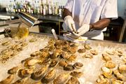 Oyster shucker Will Burris shows off some of the food that will be on the menu when the Chesapeake opens July 12.