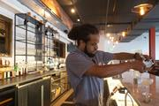 A bartender prepares a drink called the Walker-Hasslinger, which is named after the restaurant that occupied the site before the Chesapeake Restaurant. The drink is a specialty cocktail that includes lighting rosemary on fire with Everclear.