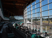 A window washer prepares the vast wall of viewing glass for opening day inside Portland Meadows HQ.