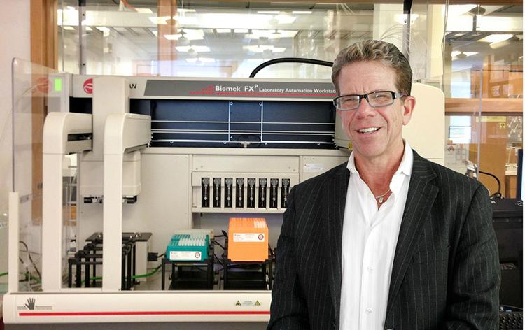 UW virus expert Dr. Michael Katze stands in front of a liquid handling robot that will process an estimated 4,000 samples per year for analysis by the functional genomics core laboratory.
