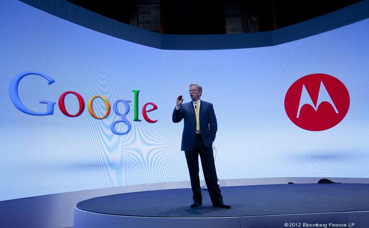 In this file photo, Eric Schmidt, executive chairman of Google, speaks in front of the Google and Motorola logos.