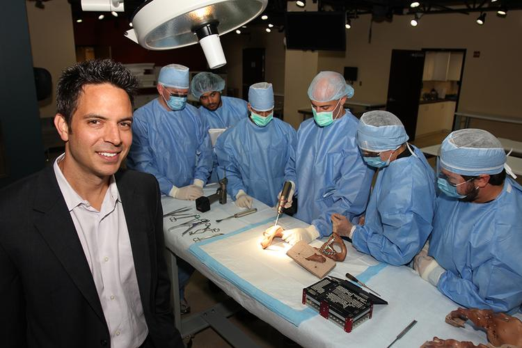 Derek Pupello, CEO, Foundation for Orthopedic Research and Education, with doctors from around the world in an orthopedic surgical training simulation. They are performing a pelvic fracture fixation.