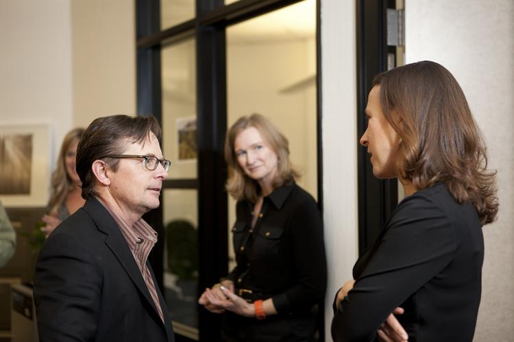 Michael J. Fox, actor and Parkinson's activist  for The Michael J. Fox Foundation for Parkinson's Research, left, speaks to Anne Wojcicki, chief executive officer of 23andMe Inc. The two organizations are working closely together to research and better understand the causes of Parkinson's disease so new and improved treatments can be developed. Photographer: Mark Tuschman/23andMe Inc. via Bloomberg