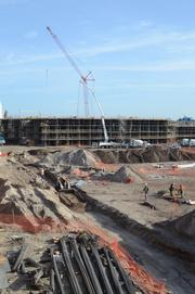 A crane and concrete boom help complete the framework and roof of building B.