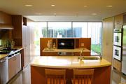 The gourmet kitchen features two islands, two dishwashers, three sinks/disposals, six burners and a built-in dining table.