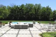 An outdoor seating area is near the pool.