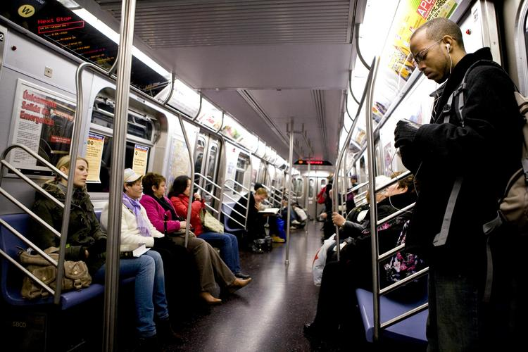 """Commuters ride a downtown """"W"""" line subway train in New York."""