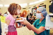 "Impending surgery on her bear requires a kiss from 7-year-old patient Madeline Smith, before the bear's ""surgeon"" Leah Dunn, CCLS, Child Life fellow, carries the bear to an imaginary operating room in Moore Auditorium. Kids at teddy bear clinic chose their bear's ""diagnosis,"" often identical to their own, allowing them to experience triage or a visit to an imaginary Lab, Pharmacy or Radiology department along with their bear."
