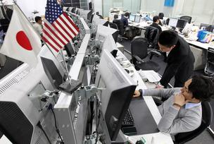 Dealers work in the trading room of Gaitame.Com Co., a foreign exchange brokerage in Japan on Monday. The yen fell against the dollar, extending losses that made it the worst-performing major currency in the past three months, after Group of 20 nations refrained from censuring Japanese policies driving the decline.