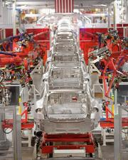 Here, Model S sedans make their way along a robotic line at the company's assembly plant.