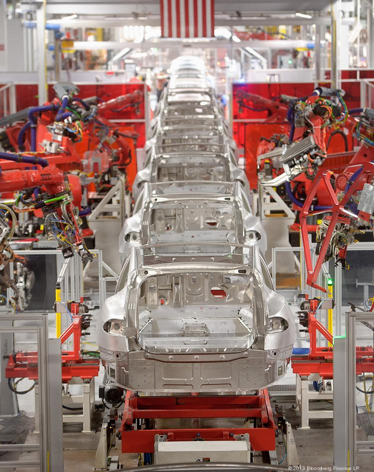 Telsa Motor Inc. Model S sedans make their way along a robotic assembly line at the company's assembly plant in Fremont, California, U.S., on Wednesday, July 10, 2013. Tesla is building Model S electric sedans faster than its initial 400-a-week goal as demand and the company's production skills increase, Chief Executive Officer Elon Musk said. Photographer: Noah Berger/Bloomberg