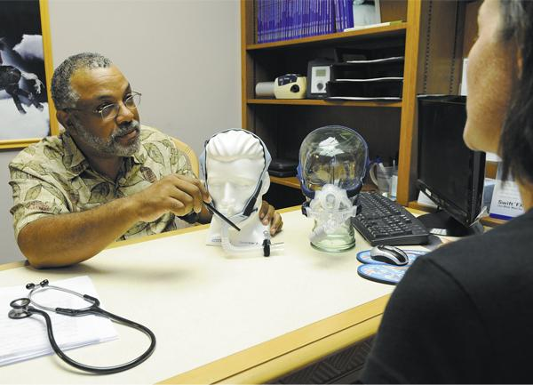 Dr. Jamil Sulieman, a physician and medical director of The Sleep Lab in Kaneohe, talks with a patient about different masks used to treat sleep apnea.