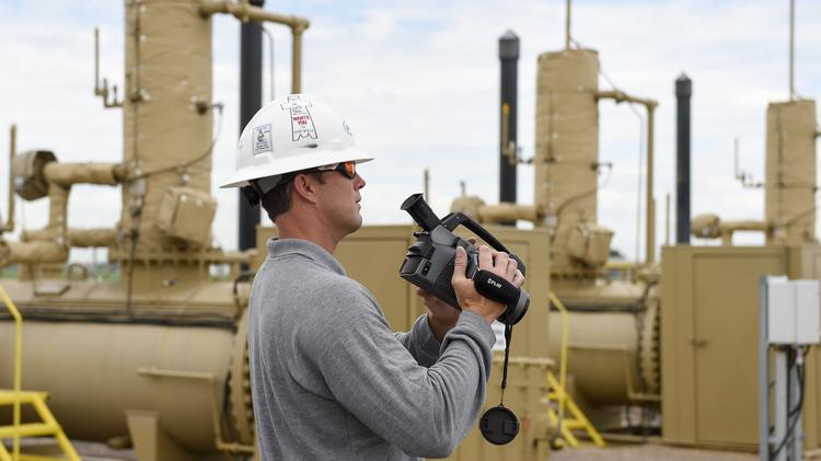Jeff Arens, emissions foreman for Anadarko Petroleum Corp., holds an infrared-sensing camera used to check oil and gas equipment for methane leaks.