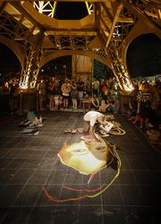 An artist works under the Eiffel Tower.