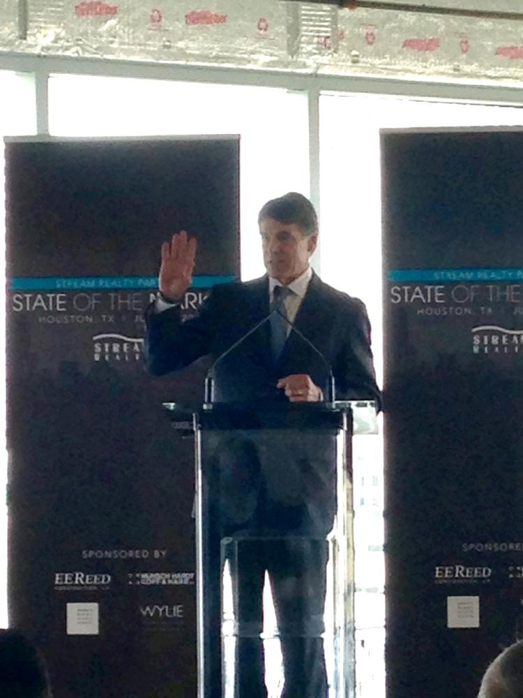 Gov. Rick Perry waves to the crowd at the Stream Realty Partners State of the Market event on July 11. Perry was the keynote speaker at the event, which drew more than 200 people.