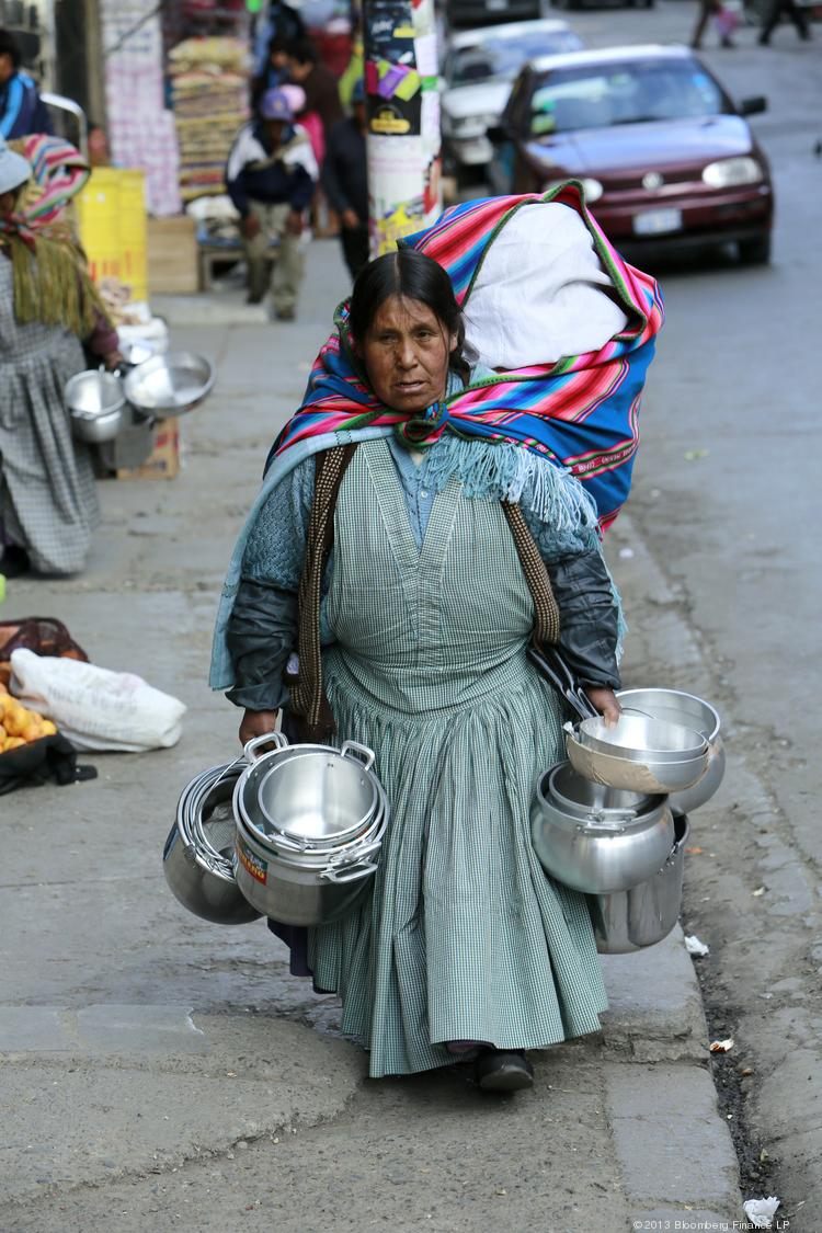 An indigenous woman carries aluminum pots at an outdoor market in La Paz, Bolivia, on Tuesday. Central bank President Marcelo Zabalaga sees inflation accelerating to 4.8 percent this year, from 4.5 percent in 2012.
