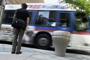 A shuttle goes by a pedestrian on the mall.