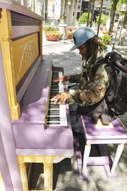 """Bruce """"Ray"""" Brown plays a piano on the mall. Colorfully painted pianos were placed back out on the 16th Street Mall as part of Your Keys to the City, a public piano art program created by the Downtown Denver Partnership. Hand-painted by local artists, each piano is available for the public to play from 8 am to 10 pm seven days a week."""
