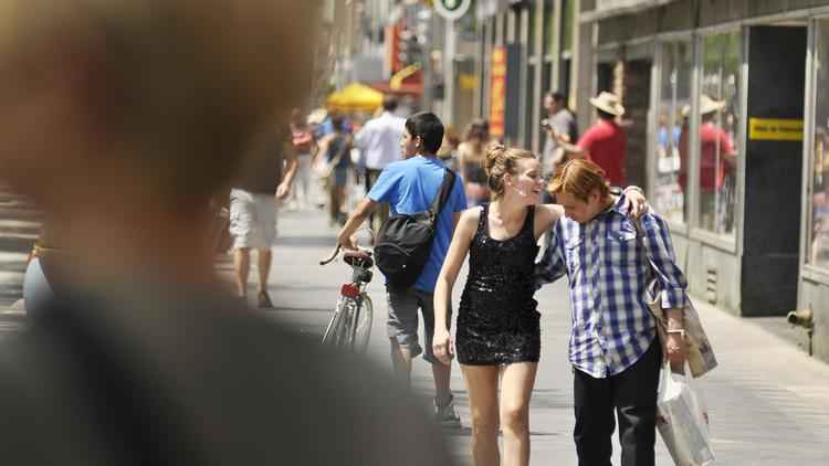 Shoppers holding retail bags walk down the 16th Street Mall in downtown Denver.
