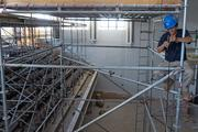 Construction workers install lights that will hang over the fitness center, which is a portion of the former auditorium.
