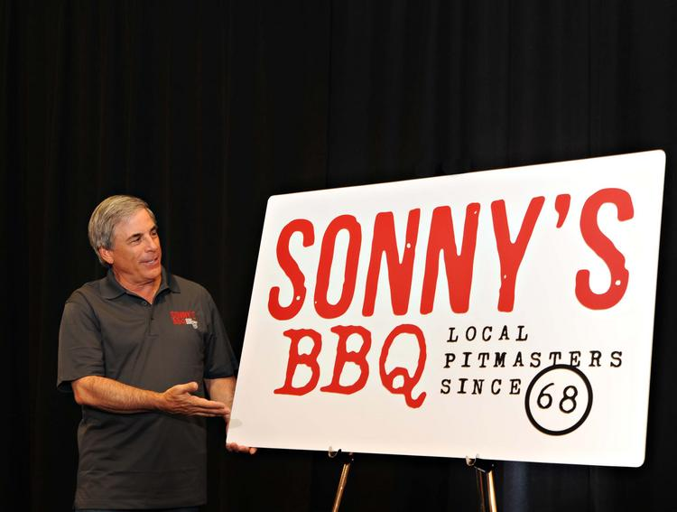 Sonny's CEO Bob Yarmuth unveils the chain's new logo to more than 600 franchise owners, vendors and corporate employees at an event in ChampionsGate.