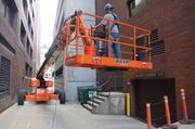 A worker maneuvers equipment through an alley behind the office.
