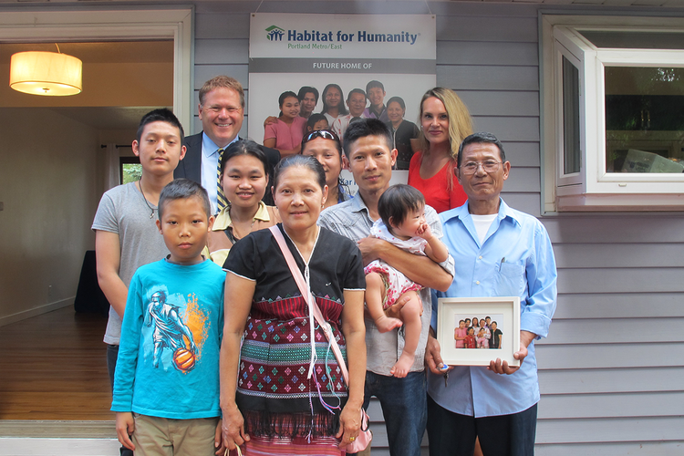 The Thet-Kar family gather in front of their new home with Larry Davis and Monique Barton from Bank of America (behind).