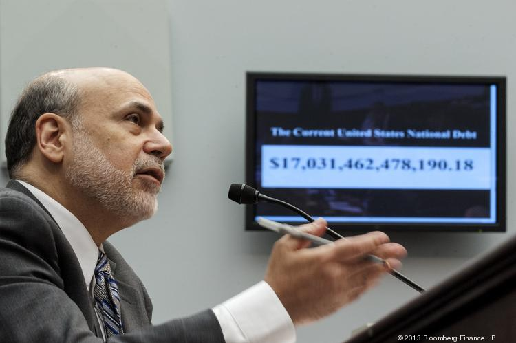 "A monitor displays the current U.S. national debt while Ben Bernanke, chairman of the U.S. Federal Reserve, delivers his semi-annual monetary policy report to the House Financial Services Committee in Washington, D.C., on Wednesday. Bernanke said the central bank's asset purchases ""are by no means on a preset course"" and could be reduced more quickly or expanded as economic conditions warrant."