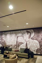 A mural consisting of thousands of album covers placed together to create an image of Hank Williams in the sitting area.