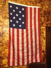 American flag replica from the Civil War era drapped on the knotty pine walls of Arsenal Cider House.