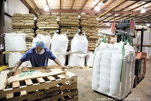 Terrance Amison unloads and stacks tea at Royal Cup's facility, where it plans a $30 million expansion.